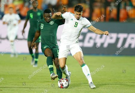 Nigeria's Oghenekaro Etebo, left, and Algeria's Baghdad Bounedjah fight for the ball during the African Cup of Nations semifinal soccer match between Algeria and Nigeria in Cairo International stadium in Cairo, Egypt