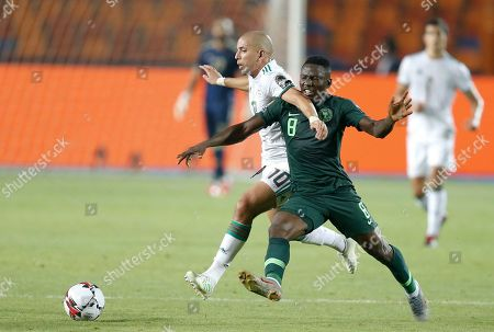 Algeria's Sofiane Feghouli, left, and Nigeria's Oghenekaro Etebo fight for the ball during the African Cup of Nations semifinal soccer match between Algeria and Nigeria in Cairo International stadium in Cairo, Egypt