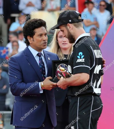 New Zealand's captain Kane Williamson receives the runners-up trophy from former Indian cricketer Sachin Tendulkar after his team lost the Cricket World Cup final match between England and New Zealand at Lord's cricket ground in London, England