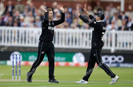 New Zealand's Lockie Ferguson, left, celebrates with Mitchell Santner after taking the wicket for England's Chris Woakes for 2 runs during the Cricket World Cup final match between England and New Zealand at Lord's cricket ground in London