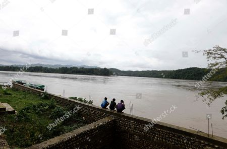 People sit on the bank of the Ayeyarwaddy river at Ayeyarwaddy Myitsone, near the Myitsone dam project, Myitkyina, Kachin State, 14 July 2019. The Myitsone Dam project began in 2009, when Myanmar was still under the rule of a junta. It was initially scheduled to be completed in 2017. China Power Investment Corporation (CPI), the contractor, had designed the dam to be the world's fifteenth largest hydroelectric power station, producing up to 6,000 megawatts of electricity. 90 percent of that power was to be exported to neighboring Yunnan province in south-west China. The dam, sitting on the Irrawaddy, Myanmar's longest river, was fiercely opposed by the Kachin Independence Organization (KIO), an armed insurgency that has been fighting for the partial autonomy of the Kachin state for the past five decades. In 2011, former Myanmar president Thein Sein announced that the project was to be suspended due to protests from locals and environmentalists.