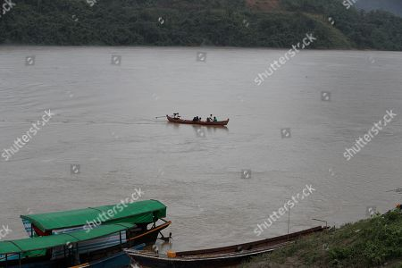 A boat passing on the Ayeyarwaddy river at Ayeyarwaddy Myitsone, near the Myitsone dam project, Myitkyina, Kachin State, 14 July 2019. The Myitsone Dam project began in 2009, when Myanmar was still under the rule of a junta. It was initially scheduled to be completed in 2017. China Power Investment Corporation (CPI), the contractor, had designed the dam to be the world's fifteenth largest hydroelectric power station, producing up to 6,000 megawatts of electricity. 90 percent of that power was to be exported to neighboring Yunnan province in south-west China. The dam, sitting on the Irrawaddy, Myanmar's longest river, was fiercely opposed by the Kachin Independence Organization (KIO), an armed insurgency that has been fighting for the partial autonomy of the Kachin state for the past five decades. In 2011, former Myanmar president Thein Sein announced that the project was to be suspended due to protests from locals and environmentalists.
