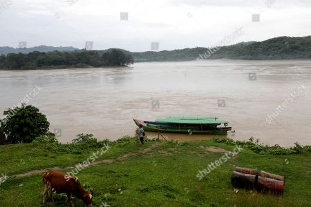 A man (C) anchored his boat at the bank of the Ayeyarwaddy river at Ayeyarwaddy Myitsone, near the Myitsone dam project, Myitkyina, Kachin State, 14 July 2019. The Myitsone Dam project began in 2009, when Myanmar was still under the rule of a junta. It was initially scheduled to be completed in 2017. China Power Investment Corporation (CPI), the contractor, had designed the dam to be the world's fifteenth largest hydroelectric power station, producing up to 6,000 megawatts of electricity. 90 percent of that power was to be exported to neighboring Yunnan province in south-west China. The dam, sitting on the Irrawaddy, Myanmar's longest river, was fiercely opposed by the Kachin Independence Organization (KIO), an armed insurgency that has been fighting for the partial autonomy of the Kachin state for the past five decades. In 2011, former Myanmar president Thein Sein announced that the project was to be suspended due to protests from locals and environmentalists.