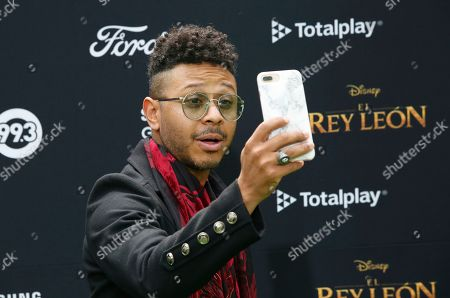 Mexican singer and actor Kalimba records himself during a red carpet event promoting the Spanish-language version of The Lion King movie in Mexico City, Mexico