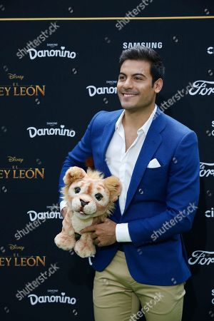 Mexican singer Carlos Rivera, who is the voice of Simba in the Spanish language version of The Lion King, poses with a stuffed animal during a red carpet event promoting the film in Mexico City