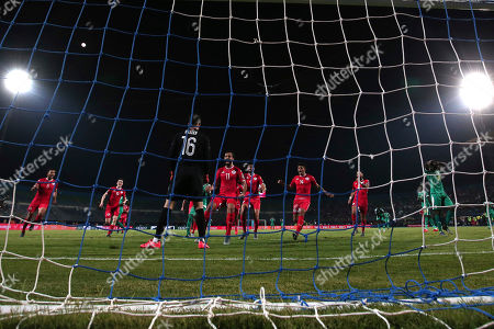 Stock Picture of Tunisia players congratulated Tunisia's Hassen Mouez after he saves a penalty from Senegal's Henri Grégoire Saivet during the African Cup of Nations semifinal soccer match between Senegal and Tunisia in 30 June stadium in Cairo, Egypt