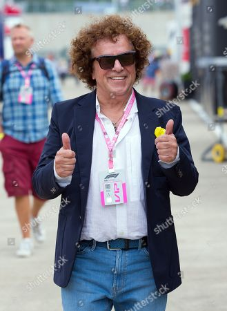 Pop star Leo Sayer walks through the paddock at Silverstone Circuit.