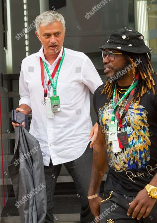 Ex football manager José Mourinho and cricketer Chris Gayle walk through the paddock at Silverstone Circuit.