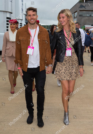 Stand up comedian Joel Dommett and girlfriend Hannah Cooper walk through the paddock at Silverstone Circuit.