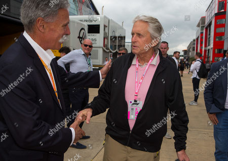 Hollywood actor Michael Douglas speaks to Chase Carey, Chief Executive Officer of the Formula One Group in the paddock at Silverstone Circuit.