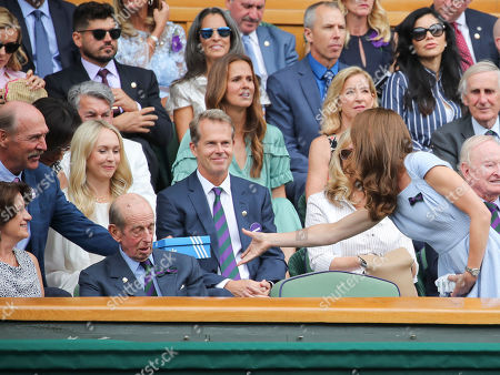 Stan Smith handing Catherine Duchess of Cambridge an Adidas trainer box in the Royal Box