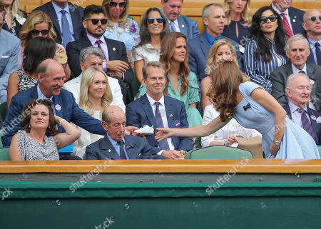 Stan Smith handing Catherine Duchess of Cambridge an Adidas trainer in the Royal Box