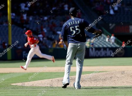Stock Photo of Roenis Elias, Matt Thaiss. Seattle Mariners relief pitcher Roenis Elias (55) looks to the outfield after giving up a three-run home run to Los Angeles Angels' Matt Thaiss, left background, during the eighth inning of a baseball game, in Anaheim, Calif