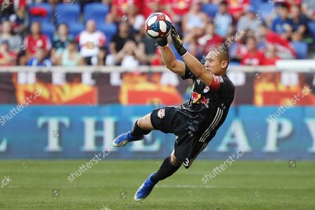 New York Red Bulls goalkeeper Luis Robles dives to make a save during the first half of an MLS soccer match against New York City FC, in Harrison, N.J
