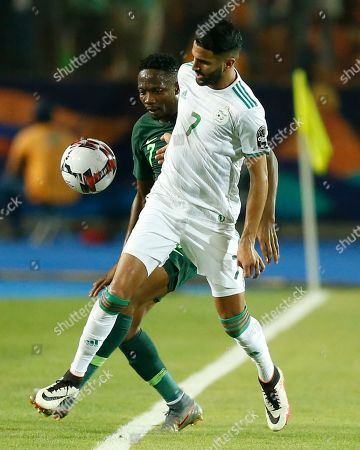 Algeria's Riyad Mahrez, front, fights for the ball with Nigeria's Ahmed Musa during the African Cup of Nations semifinal soccer match between Algeria and Nigeria in Cairo International stadium in Cairo, Egypt