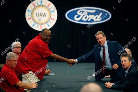 Stock Image of United Auto Workers Vice President Rory Gamble, left, and Ford Motor Co., Executive Chairman Bill Ford shake hands to open their contract talks, in Dearborn, Mich
