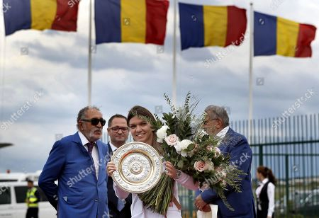 Romania's Simona Halep (C) holds the Wimbledon Championships singles trophy, as she arrives at the Henri Coanda International Airport, 20 Km north from Bucharest, Romania, 14 July 2019. Halep is the first Romanian tennis player ever to win a Wimbledon singles title. On the left is former tennis player and manager and businessman Ion Tiriac.