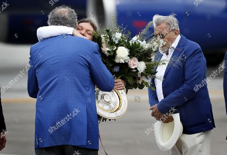 Romania's Simona Halep (C), is embraced by former tennis player Ion Tiriac (L), assisted by former tennis star Ilie Nastase (R),  as she arrives at the Henri Coanda International Airport, 20 Km north from Bucharest, Romania, 14 July 2019. Halep is the first Romanian tennis player ever to win a Wimbledon singles title. On the left is former tennis player and manager and businessman Ion Tiriac.