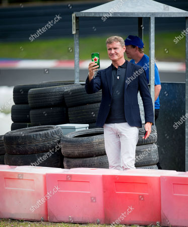 David Coulthard takes pictures on a phone as drivers pass by on the track