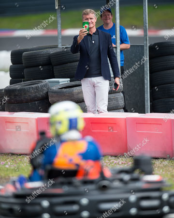 Former F1 driver David Coulthard takes a picture on his phone whilst watching the racing on the track