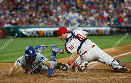 J.T. Realmuto, Austin Barnes. Los Angeles Dodgers' Austin Barnes, left, steals home past Philadelphia Phillies catcher J.T. Realmuto during the fourth inning of a baseball game, in Philadelphia