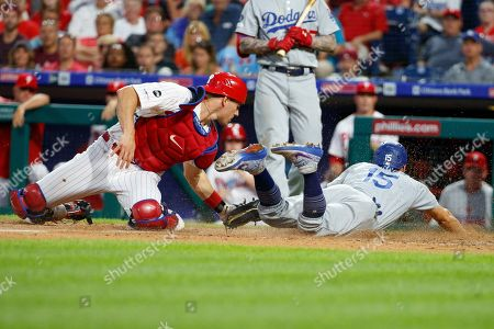 Los Angeles Dodgers catcher Austin Barnes (15) steals on to score before Philadelphia Phillies catcher J.T. Realmuto (10) could apply the tag during the MLB game between the Los Angeles Dodgers and Philadelphia Phillies at Citizens Bank Park in Philadelphia, Pennsylvania