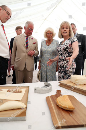 Stock Image of Production Director, Julie Roberts shows Prince Charles and Camilla Duchess of Cornwall around the bakery ahead of a garden party to celebrate the 50th anniversary of Ginsters Bakery in Callington