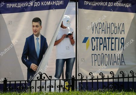 Stock Photo of A campaign worker looks at her mobile phone inside the tent of the 'Ukrainian strategy of Groysman' party of the acting Prime Minister Volodymyr Groysman, in Kiev, Ukraine, 16 July 2019. Elections will be held on 21 July 2019 after President Volodymyr Zelensky dissolved parliament during his inauguration on 21 May 2019.