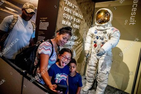 Stock Image of Charles Simpson, Queli Simpson, Giulaiana Simpson, Grayson Simpson. From left, Charles and Queli Simpson and their children Giuliana, 7, and Grayson, 5, of Orlando, Fla., take a photo together as some of the first visitors to view Neil Armstrong's Apollo 11 spacesuit after it is unveiled at the Smithsonian's National Air and Space Museum on the National Mall in Washington