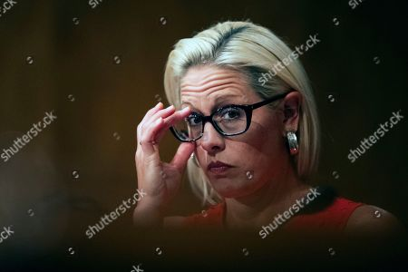 Stock Image of Kyrsten Sinema, Steven Dillingham, Robert Goldenkoff, Nicholas Marinos. Senate Security and Governmental Affairs Committee member Sen. Kyrsten Sinema, D-Ariz., adjusts her eyeglasses during a hearing on 2020 census on Capitol Hill in Washington