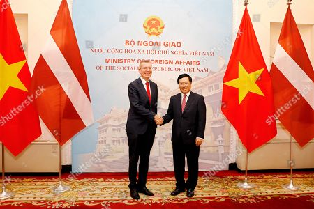 Vietnam's Minister of Foreign Affairs Pham Binh Minh (R) and Edgars Rinkevics (L), Minister for Foreign Affairs of Latvia, shake hands during meeting at the Government Guesthouse in Hanoi, Vietnam, 17 July 2019. Rinkevics is on an official visit to Vietnam from 16 July to 17 July 2019.