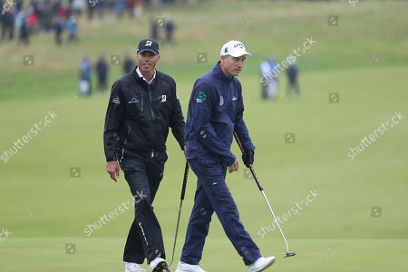 Matt Kuchar of the United States, left with Jim Furyk of the United States walk together on the 3rd green during a practice round ahead of the start of the British Open golf championships at Royal Portrush in Northern Ireland, . The British Open starts Thursday