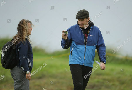 Nick Faldo a three time Open Championship winner takes a photo with his smart phone on the 15th green as he walks the course ahead of the start of the British Open golf championships at Royal Portrush in Northern Ireland, . The British Open starts Thursday