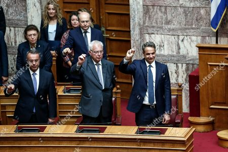 Stock Image of Greek Prime Minister Kyriakos Mitsotakis, right, Deputy Prime Minister Panagiotis Pikrammenos, center, and Finance Minister Christos Staikouras, left, take the oath during a swearing in ceremony at the parliament in Athens, . Greece held its first parliamentary session after the general elections held on July 7