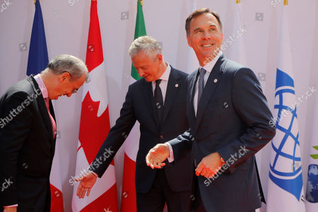 French Finance Minister Bruno Le Maire, center, welcomes Canada's Finance Minister Bill Morneau, right, with Governor of the Bank of France Francois Villeroy de Galhau, at the G-7 Finance .The top finance officials of the Group of Seven rich democracies are arriving at Chantilly, at the start of a two-day meeting aimed at finding common ground on how to tax technology companies and on the risk from new digital currencies