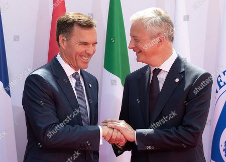 French finance minister Bruno Le Maire (R)  greets Canadian finance minister Bill Morneau as he arrives for the G7 Finance Summit in Chantilly, France, 17 July 2019.
