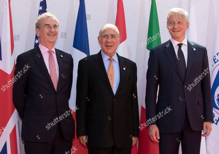 French finance minister Bruno Le Maire (R) and Governor of the Bank of France, Francois Villeroy de Galhau (L) greet Secretary-General of the Organization for Economic Cooperation and Development (OECD), Jose Angel Gurria