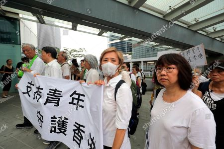Stock Picture of Veteran actress and singer Deannie Ip, center, wears a mask as she holds a banner in support of young people during a march in Hong Kong on . Some 2,000 Hong Kong senior citizens, including the popular actress, marched Wednesday in a show of support for youths at the forefront of monthlong protests against a contentious extradition bill in the semi-autonomous Chinese territory
