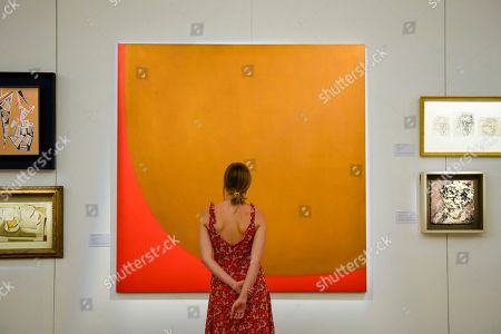 """A staff member views """"9-1960 (Red Off Cut"""", 1960, by William Turnbull"""