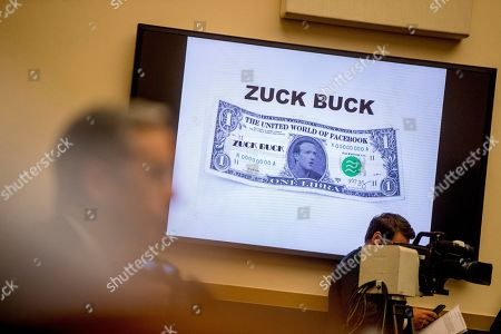"Facebook CEO Mark Zuckerberg's face is visible on a mock ""Zuck Buck"" depicted on a screen as David Marcus, CEO of Facebook's Calibra digital wallet service, foreground, is questioned by Rep. Brad Sherman, D-Calif., during a House Financial Services Committee hearing on Facebook's proposed cryptocurrency on Capitol Hill in Washington"
