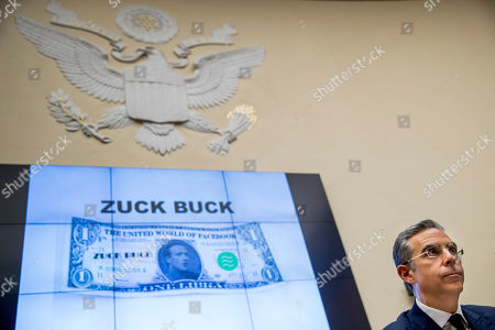 "Facebook CEO Mark Zuckerberg's face is visible on a mock ""Zuck Buck"" depicted on a screen behind David Marcus, CEO of Facebook's Calibra digital wallet service, as he is questioned by Rep. Brad Sherman, D-Calif., during a House Financial Services Committee hearing on Facebook's proposed cryptocurrency on Capitol Hill in Washington"