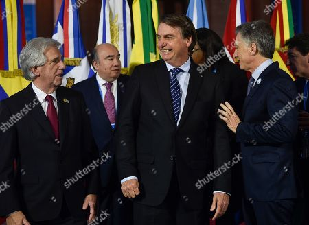 Brazil's President Jair Bolsonaro, center, stands between Uruguay's Presidente Tabare Vazquez, left, and Argentina's President Mauricio Macri during a photo opportunity at the Mercosur Summit in Santa Fe, Argentina, . The South American trading bloc that includes founding members Brazil, Argentina, Paraguay, and Uruguay, is one of the world's largest