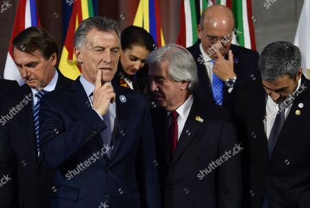 Argentina's President Mauricio Macri rubs his face as he stands in front of Brazil's President Jair Bolsonaro, left, Uruguay's President Tabare Vazquez, behind center right, and Paraguay's President Mario Abdo Benitez, right, as they gather for a group photo at the Mercosur Summit in Santa Fe, Argentina, . The South American trading bloc that includes founding members Brazil, Argentina, Paraguay, and Uruguay, is one of the world's largest
