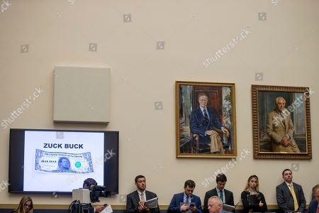 "Congressional aides stand along a wall where Facebook CEO Mark Zuckerberg's face is visible on a mock ""Zuck Buck"" depicted on a screen as David Marcus, CEO of Facebook's Calibra digital wallet service, is questioned by Rep. Brad Sherman, D-Calif., during a House Financial Services Committee hearing on Facebook's proposed cryptocurrency on Capitol Hill in Washington"