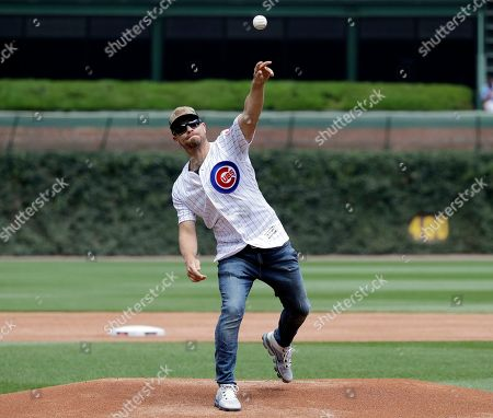 Country music artist Dustin Lynch throws out a ceremonial first pitch before a baseball game between the Cincinnati Reds and the Chicago Cubs in Chicago