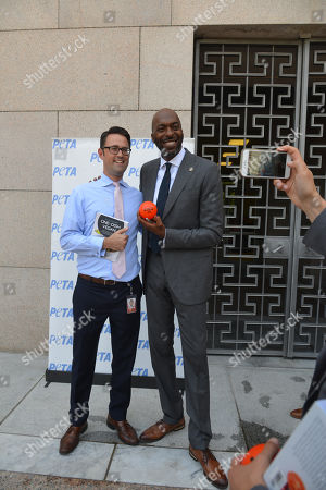 Stock Image of John Salley poses with a House staff member at the annual PETA (People for the Ethical Treatment of Animals) veggie dog lunch in front of the Rayburn House office building. PETA provided meat free hot dogs to crowds outside the building.