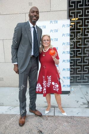 Stock Photo of John Salley poses with Congresswoman Debbie Dingal, D-MI at the annual PETA (People for the Ethical Treatment of Animals)Veggie dog lunch in front of the Rayburn House office building. PETA provided meat free hot dogs to crowds outside the building.
