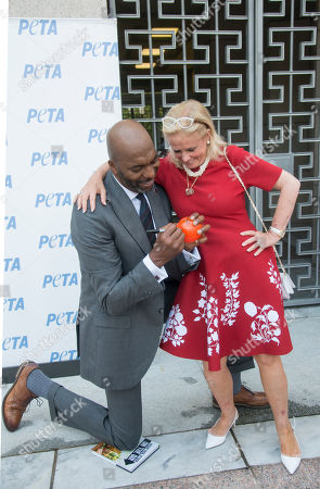 Stock Picture of John Salley poses with Congresswoman Debbie Dingal, D-MI at the annual PETA (People for the Ethical Treatment of Animals) Vwggie Dog lunch.in front of the Rayburn House office building. Salley signed a small plastic basketball for her.PETA provided meat free hot dogs to crowds outside the building.