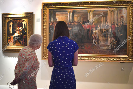 Stock Photo of Queen Elizabeth II looks at a painting of Queen Victoria inspecting wounded Coldstream Guardsmen, 1855, by John Gilbert, alongside Lucy Peter, assistant curator as part of the exhibition to mark the 200th anniversary of the birth of Queen Victoria for the Summer Opening of Buckingham Palace