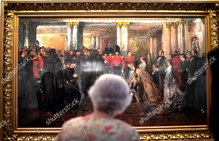 Stock Image of Queen Elizabeth II looks at a painting of Queen Victoria inspecting wounded Coldstream Guardsmen, 1855, by John Gilbert, as part of the exhibition to mark the 200th anniversary of the birth of Queen Victoria for the Summer Opening of Buckingham Palace